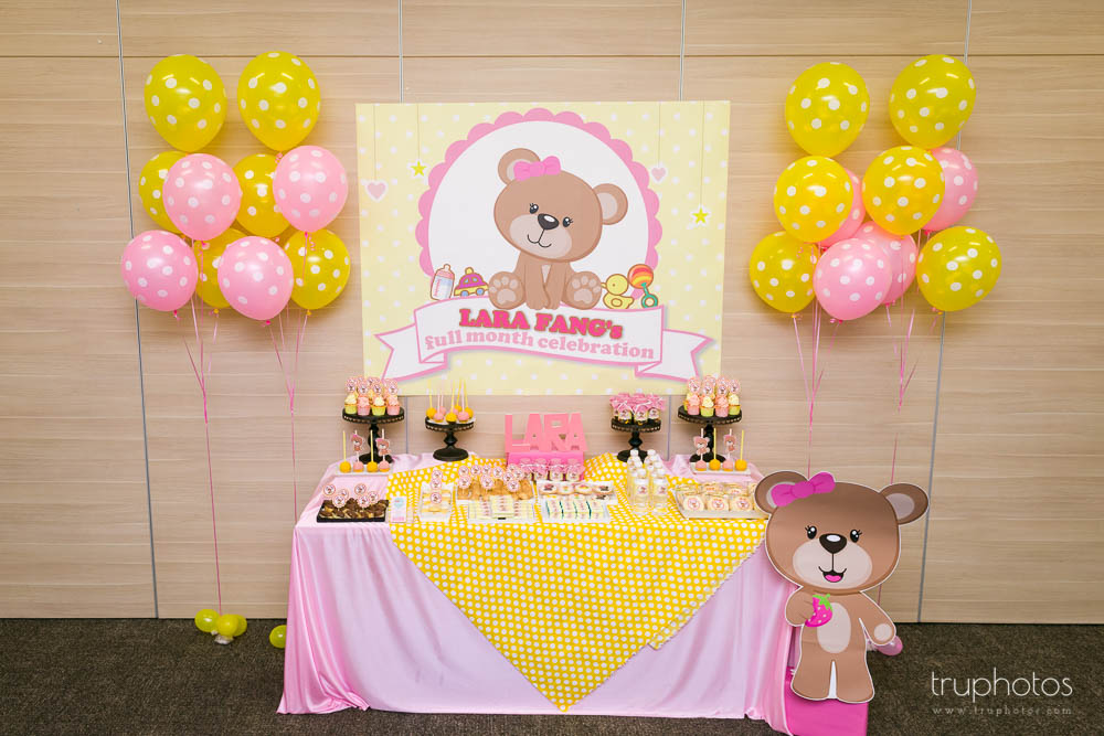 Overall look of cute teddy bear theme birthday party dessert table with fun coloured balloons