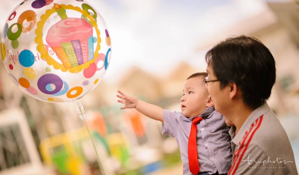 Birthday baby reaching out for balloon at first birthday party | Singapore children birthday party, baby shower photography by Truphotos